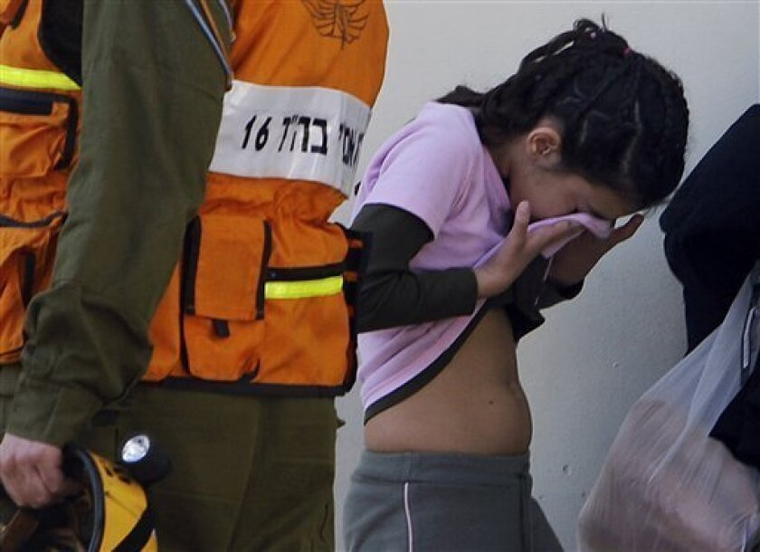 An Israeli girl wipes tears as her school is evacuated after a rocket, fired from the Gaza Strip, hit a house next to a school in the Israeli southern city of Sderot, Sunday, Jan. 11, 2009. Israeli troops battled Palestinian gunmen in a suburb of Gaza City Sunday in one of the fiercest ground battl