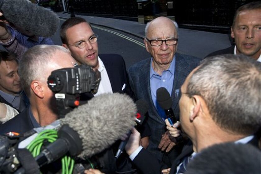 Chairman of News Corporation Rupert Murdoch, center right, and his son James Murdoch, center left, chief executive of News Corporation Europe and Asia face the media as they arrive at his residence in central London, Sunday, July 10, 2011. News of the World cease publication with Sunday issue the last. News of the World is accused of hacking into the mobile phones of various crime victims, celebrities and politicians. (AP Photo/Sang Tan)