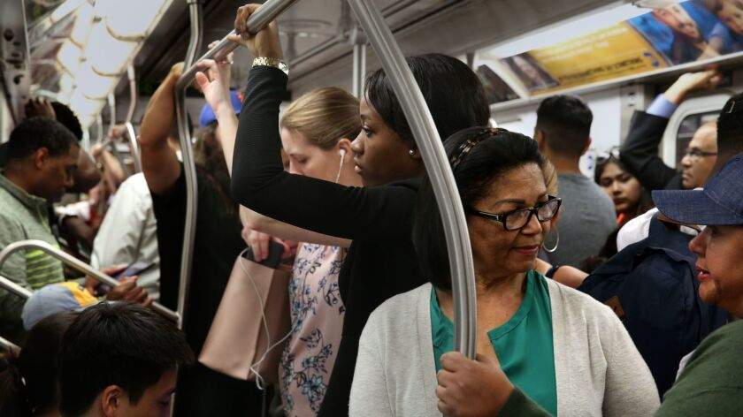 Passengers wait during a delay on the express No. 4 train as it goes uptown on June 28. Train delays