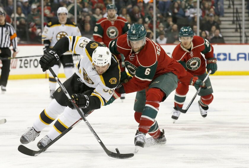 Boston Bruins left wing Matt Beleskey (39) and Minnesota Wild defenseman Marco Scandella (6) chase the puck during the second period of an NHL hockey game in St. Paul, Minn., Saturday, Feb. 13, 2016. (AP Photo/Ann Heisenfelt)