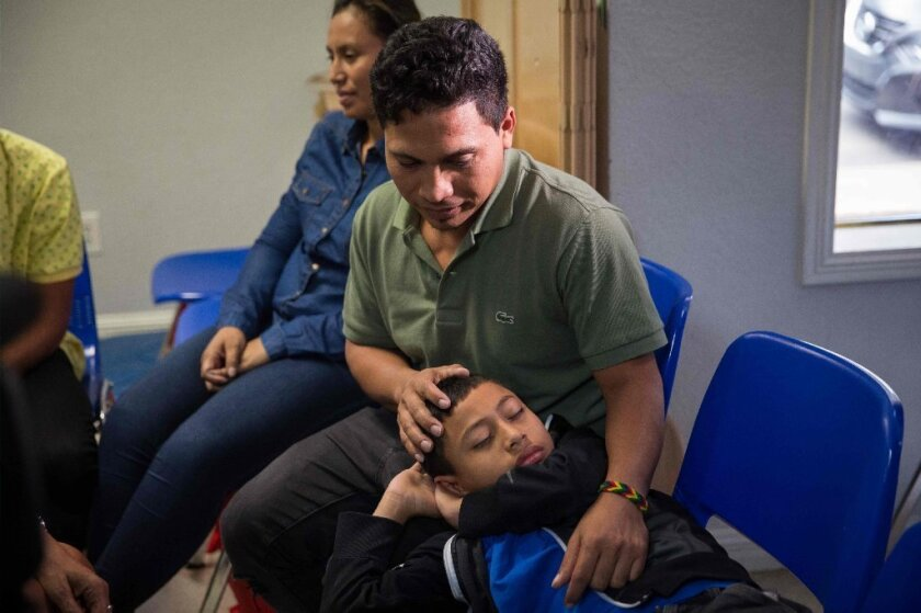 In this file photo taken on June 17, 2018, an immigrant from El Salvador and his 10-year-old son pass the time after being released from detention in McAllen, Texas. The man said he was separated from his son while in detention.