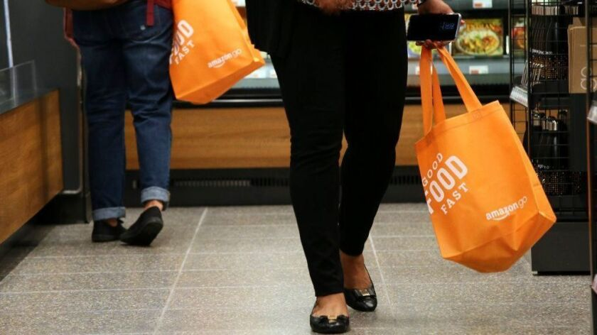 Shoppers swing bright orange bags as they shop at the new Amazon Go store Monday in the Loop. (Stacey Wescott/Chicago Tribune)