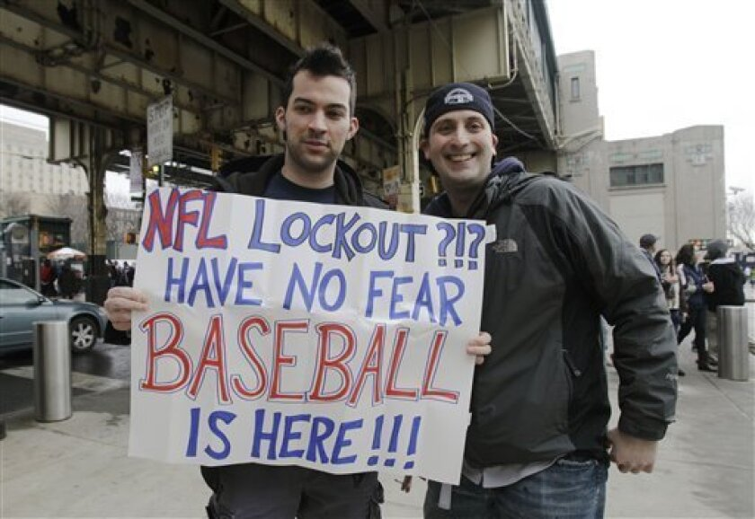 Michael Vivalo, left, and Chaplain Warren show off their sign beneath the subway platform before the Yankees faced the Detroit Tigers in their opening day baseball game at Yankee Stadium on Thursday, March 31, 2011 in New York. (AP Photo/Kathy Willens)