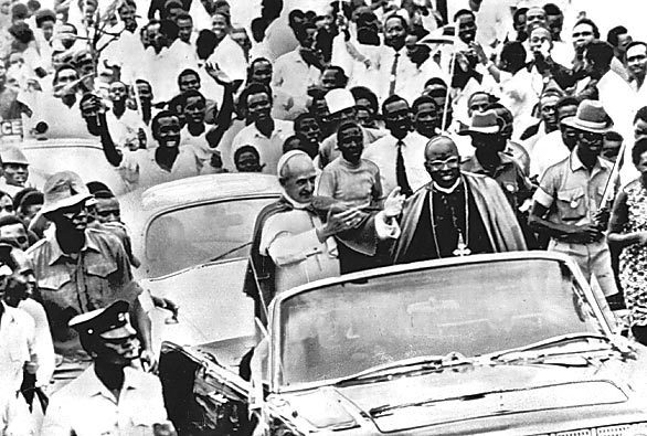 In August 1969, Pope Paul VI acknowledges the crowd from an open car on his way to Kampala, Uganda.