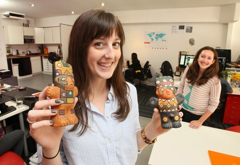 Anna Watt, a project manager at thinkPARALLAX communications firm in downtown Encinitas, holds two souvenir statues she brought back from her recent vacation to Machu Picchu, Peru. At right is co-worker Julia McCann.