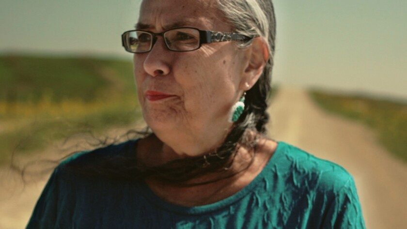 """Sandy White Hawk, who is featured in the documentary """"Blood Memory,"""" walks the """"road of her past"""" in Rosebud, S.D."""
