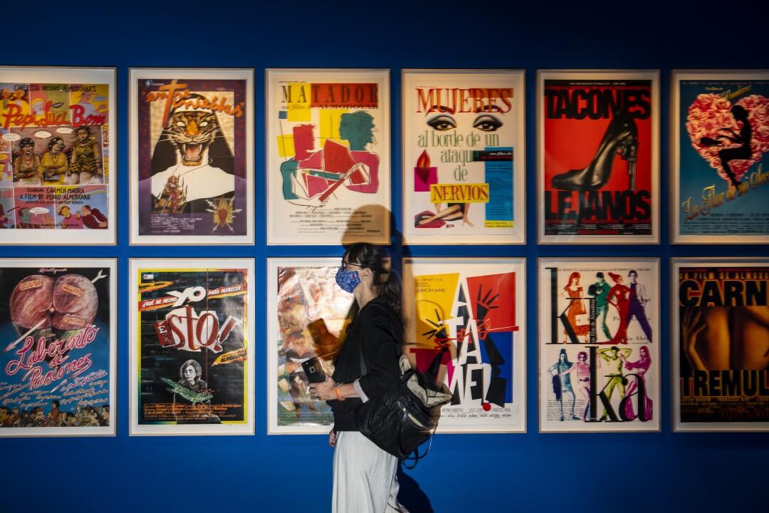Una persona que lleva una máscara pasa frente a una pared cubierta de carteles.