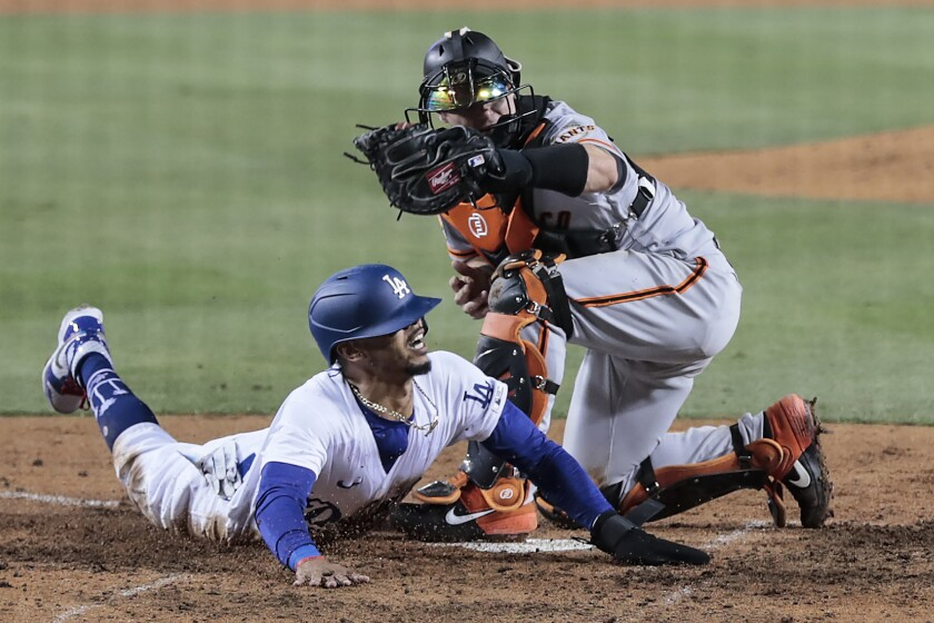 Dodgers right fielder Mookie Betts (50) slides safely into home by avoiding the tag of Giants catcher Tyler Heineman.