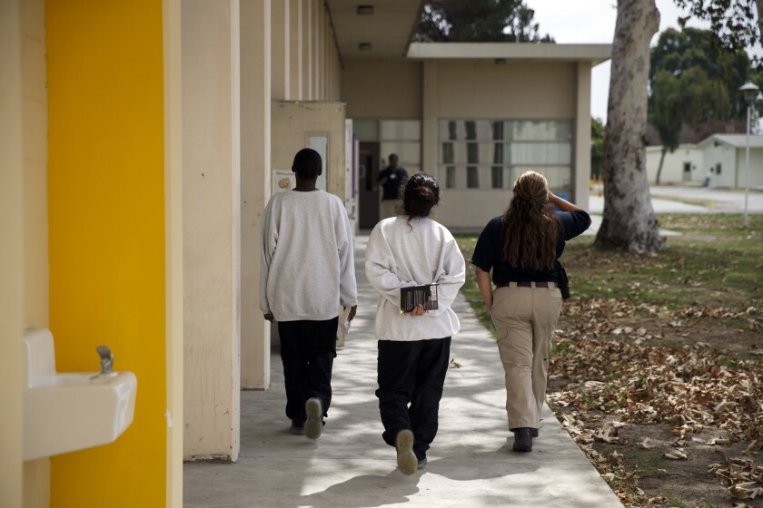 """Female detainees carry books from the library. """"In my own way, I'm doing my own civil rights initiative,"""" said Gallegos, who advocated for the library to inspire the readers she teaches in the juvenile hall."""