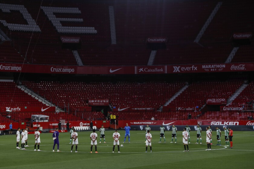 Sevilla and Betis players stand during a minute of silence before the start of their Spanish La Liga soccer match in Seville, Spain, Thursday, June 11, 2020. With virtual crowds, daily matches and lots of testing for the coronavirus, soccer is coming back to Spain. The Spanish league resumes this week more than three months after it was suspended because of the pandemic, becoming the second top league to restart in Europe. The Bundesliga was first. The Premier League and the Italian league should be next in the coming weeks. (AP Photo)