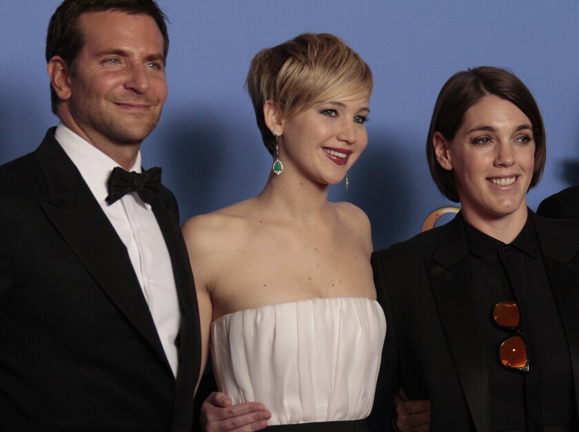 """""""American Hustle"""" stars Bradley Cooper and Jennifer Lawrence with Megan Ellison (right) at the 71st Annual Golden Globe Awards."""
