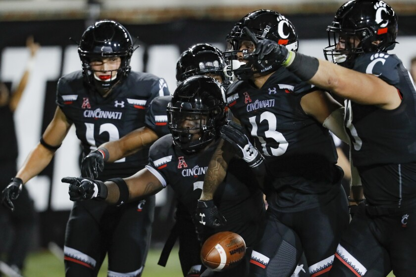 Cincinnati wide receiver Trent Cloud (13) celebrates with his teammates after scoring a first-half touchdown against Central Florida on Friday.
