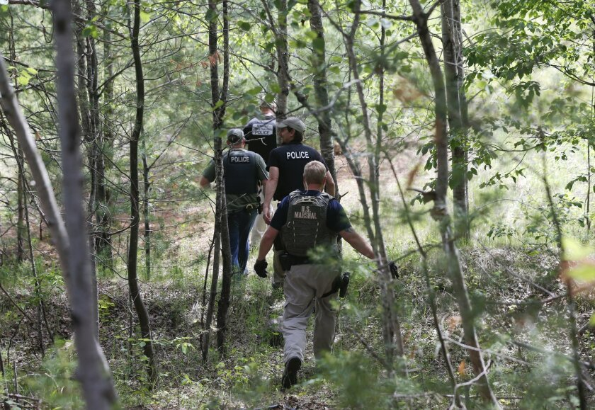 Law enforcement officers walk into the woods behind a residence while searching for escaped prisoners David Sweat and Richard Matt on Sunday, June 14, 2015, in Cadyville, N.Y. Law enforcement personnel are in the ninth day of searching for Sweat and Matt, two killers who used power tools to cut the