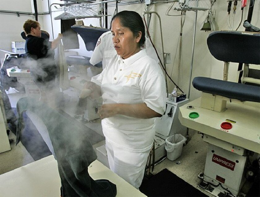 Sweat-soaked Elena Hidalgo operated a steam presser  yesterday at Continental Dry Cleaners on Broadway in San  Diego. Relief is expected today. (Earnie Grafton / Union-Tribune)