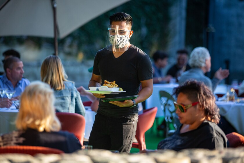 A server in a mask and face shield carries food to a table of diners at an outdoor seating area