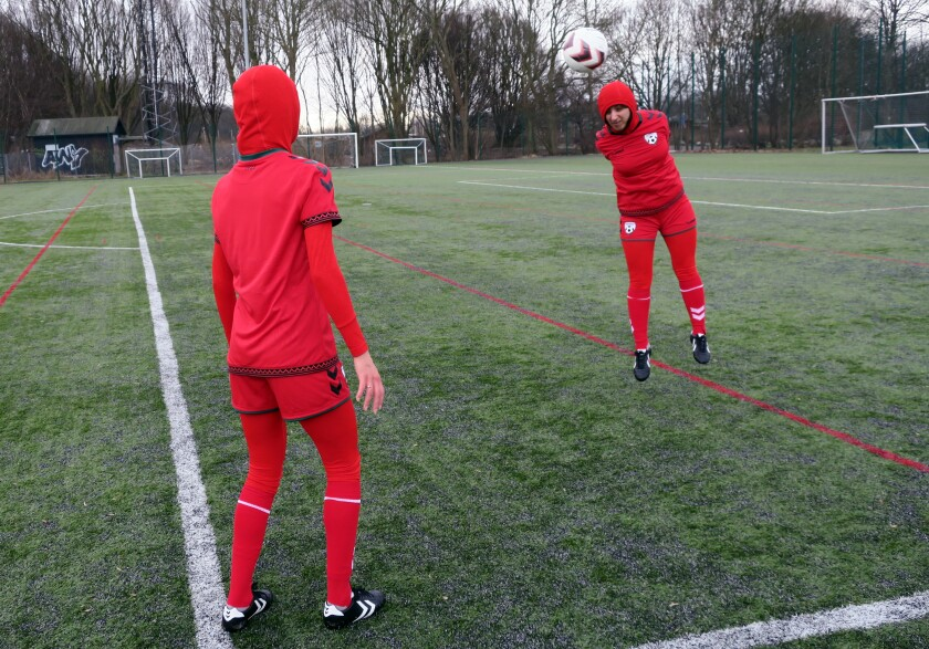 Shabnam Mabarz, seen from behind, watches as Khalida Popal heads the ball