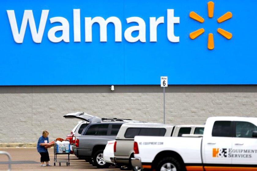 Una mujer coloca suministros en su coche en el estacionamiento de un Walmart en Pearl, Mississippi.