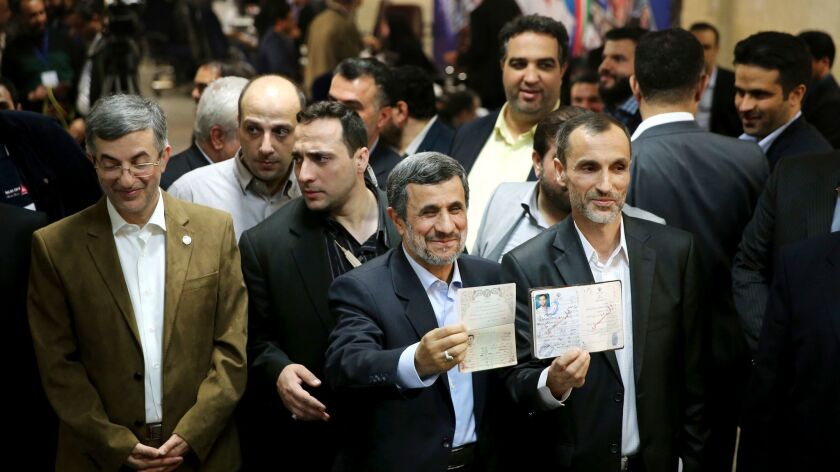 Former Iranian President Mahmoud Ahmadinejad, center, and ally Hamid Baghaei, right, show their identifications Apil 12 after registering for presidential elections.