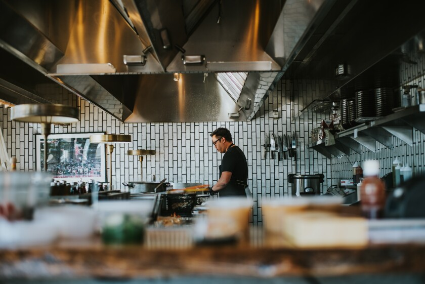 An employee works alone in Underbelly restaurant in North Park in this photo from Lindsay Kreighbaum's photo essay on restaurants operating during the COVID-19 pandemic.