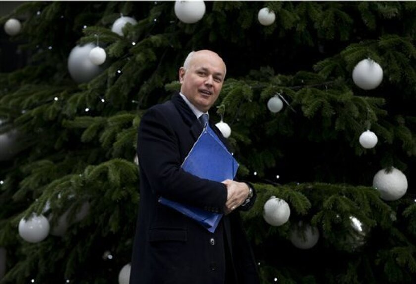 FILE - In this Dec. 4, 2012 file photo, Britain's Secretary for Work and Pensions Iain Duncan Smith looks to the media as he walks past the Christmas tree in Downing Street ahead of a cabinet meeting in London. Opponents of a raft of welfare changes want Smith to make good on a claim that he could live on the 53 pounds ($80) a week that one benefits recipient says he has left over after paying for housing and heat. (AP Photo/Alastair Grant, File)