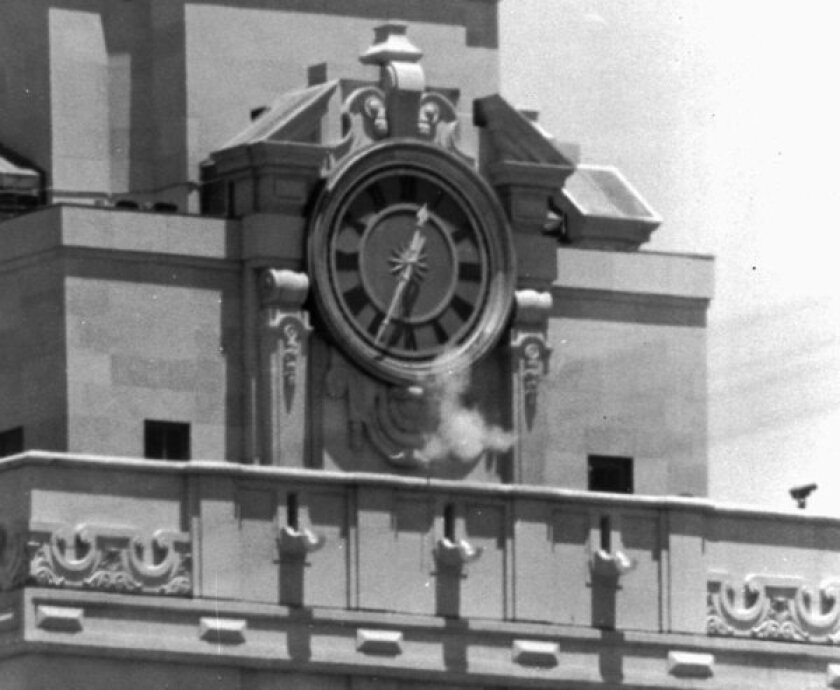 Smoke from a sniper's gun is seen as Charles Whitman fires from the tower of the University of Texas administration building in Austin on Aug. 1, 1966, part of a rampage in which he killed 15 people, including a pregnant woman.