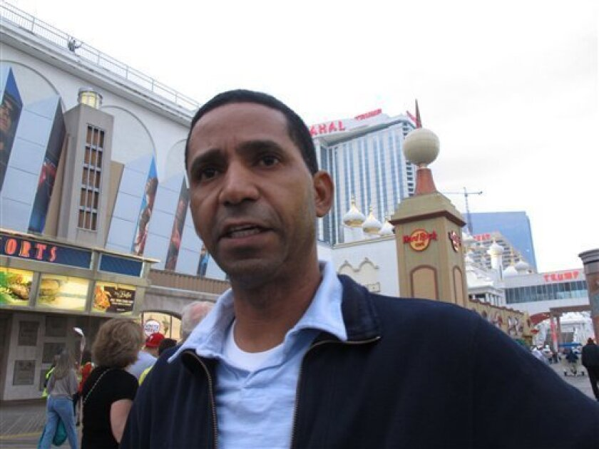 In a Sept. 30, 2011 photo, Marcos Vidal, a housekeeper at Resorts Casino Hotel in Atlantic City, N.J., poses for a photo on the Atlantic City, N.J., Boardwalk. Vidal has seen his pay cut from $14.55 an hour to $9.83. Vidal says he has had to eliminate cable TV, Internet service, long-distance calls, sending money to his mother in the Dominican Republic, and even going to the movies. (AP Photo/Wayne Parry)