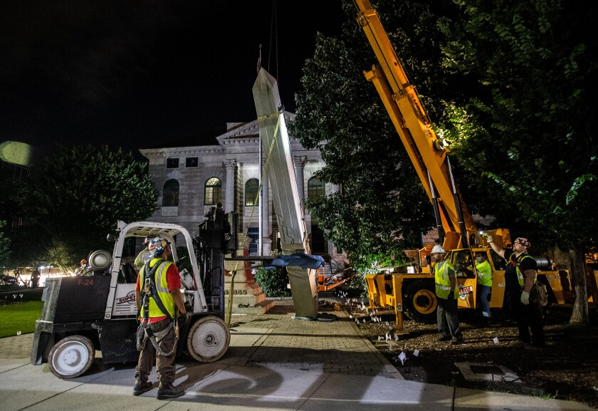 Workers remove a Confederate monument with a crane Thursday, June 18, 2020, in Decatur, Ga. The 30-foot obelisk in Decatur Square, erected by the United Daughters of the Confederacy in 1908, was ordered by a judge to be removed and placed into storage indefinitely. (AP Photo/Ron Harris)