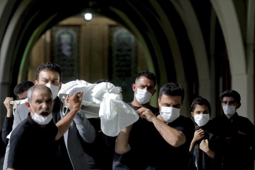 Varias personas cargan con el cuerpo de un fallecido por COVID-19 en el cementerio de Behesht-e-Zahram