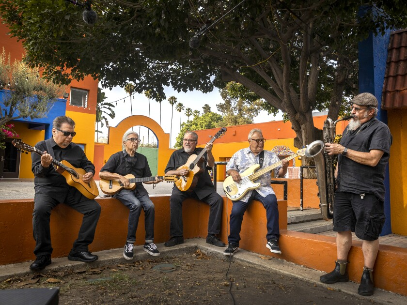Five members of the band Los Lobos hold musical instruments.