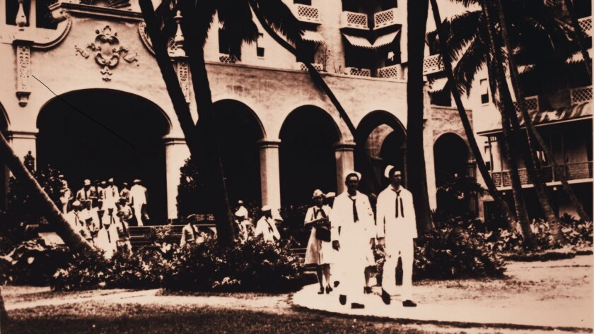 Sailors and nurses stroll the Royal Hawaiian Resort's grounds during World War II, when the Navy used it as a center for rest and relaxation for war-weary members of the military.