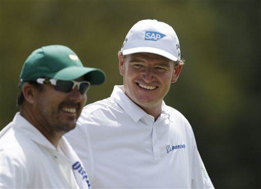 Ernie Els , of South Africa, chats with his caddie Colin Byrne on the third green during a practice round for the Masters golf tournament Tuesday, April 9, 2013, in Augusta, Ga. (AP Photo/Darron Cummings)