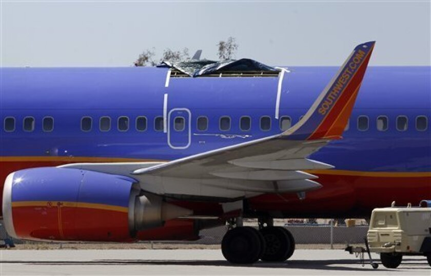FILE - In this April 4, 2011 file photo, a Southwest Airlines plane sits in a remote area of the Yuma International Airport, after the plane had a section of fuselage tear from the plane during a flight on Friday, April 1, in Yuma, Ariz. Most travelers don't think twice about the age of their aircraft. But after a five-foot hole opened in the roof of a 15-year-old Southwest jet many fliers are asking: How old is too old?(AP Photo/Ross D. Franklin, file)