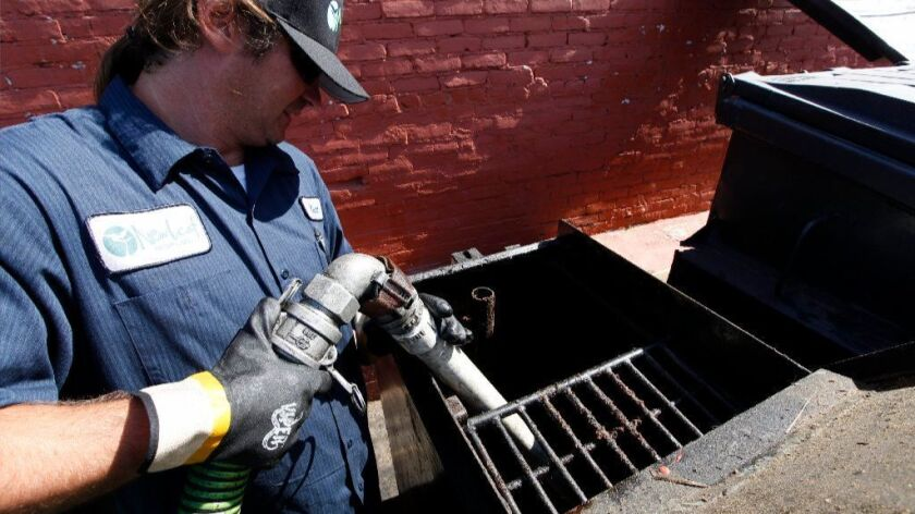 A New Leaf biofuel driver pumps used cooking oil from a restaurant holding tank. The oil is turned into biodiesel fuel.