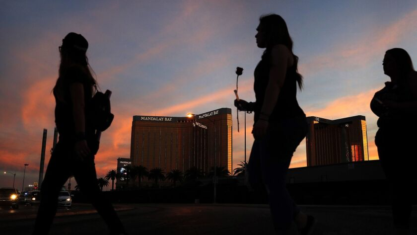 FILE - In this April 1, 2018, file photo, people carry flowers as they walk near the Mandalay Bay ho