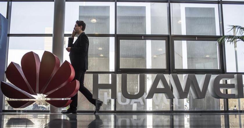 Fotografía de archivo que muestra a un hombre junto al logotipo de Huawei. EFE/Archivo