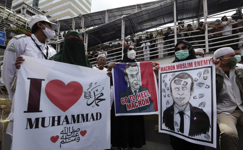 Indonesian Muslims protesters hold posters condemning French President Emmanuel Macron during an anti-France rally outside the France embassy in Jakarta, Indonesia, Monday, Nov. 2, 2020. Indonesian Muslims marched to the heavily guarded France Embassy in Indonesia's capital on Monday to protest France's president and his staunch support of secular laws that deem caricatures depicting the Prophet Muhammad as protected speech.(AP Photo/Achmad Ibrahim)