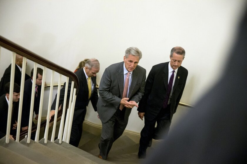 House Majority Leader Kevin McCarthy, R-Bakersfield, center, accompanied by House Armed Services Committee Chairman Rep. Mac Thornberry, R-Texas, right, walks to the House to vote on a stopgap spending bill to avert a government shutdown, Wednesday. Just hours before a midnight deadline, a bitterly