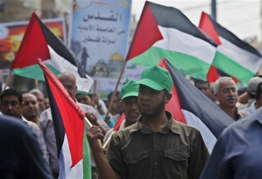 Palestinians wave their national flags during a protest to condemn what protesters claim was a desecration of Al-Aqsa Mosque in Jerusalem by Jewish extremists, in Gaza City, Wednesday, Sept. 4, 2013. Israeli police spokesman Micky Rosenfeld says that clashes in Jerusalem erupted Wednesday when some 300 Palestinian demonstrators tried to block a group of visitors from reaching the sensitive hilltop compound revered by both Jews and Muslims. Israeli police arrested seven Palestinians after clashes