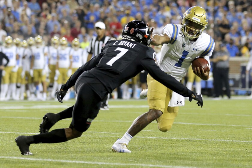 UCLA quarterback Dorian Thompson-Robinson tries to fend off Cincinnati cornerback Coby Bryant during the second half of the Bruins' 24-14 loss Thursday.