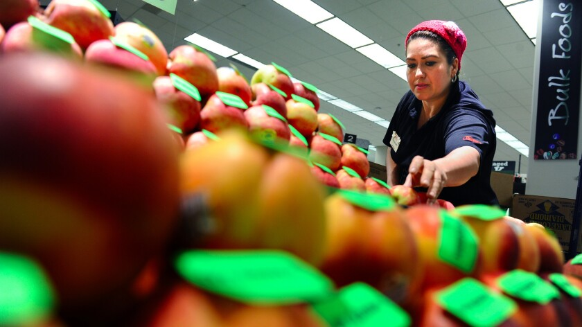A clerk stocks apples in a Ralphs store in downtown Los Angeles.