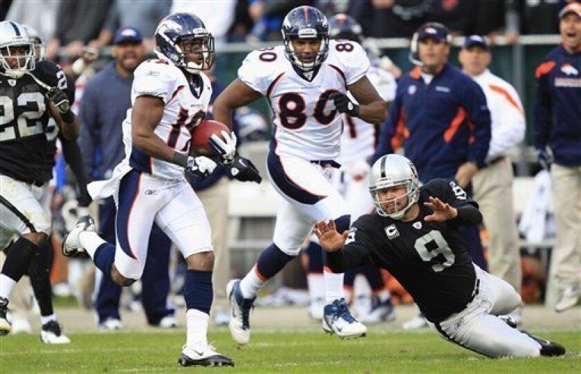 Denver Broncos wide receiver Eddie Royal (19) runs past Oakland Raiders punter Shane Lechler (9) while scoring on an 85-yard punt-return touchdown in the fourth quarter of an NFL football game in Oakland, Calif., Sunday, Nov. 6, 2011. (AP Photo/Marcio Jose Sanchez)