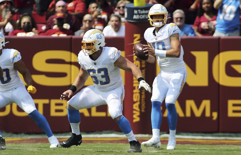 Chargers center Corey Linsley (63) checks for opposing pass rushers after snapping the ball.