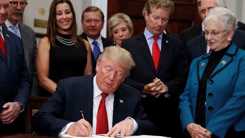 President Trump signs an executive order undermining the Affordable Care Act in the Oval Office, on Oct. 12.