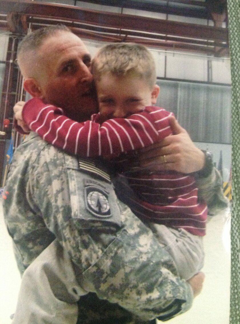 In this 2009 photo provided by Tanya Bartholomew, her husband, former army soldier, Clark Bartholomew, is seen carrying their son Aric at Fort Drum, N.Y. The former soldier's lawsuit alleging he bit into needles in a Burger King sandwich purchased at Hawaii's Schofield Barracks in 2010 is headed to trial in August after a settlement couldn't be reached. (AP Photo/Tanya Bartholomew)