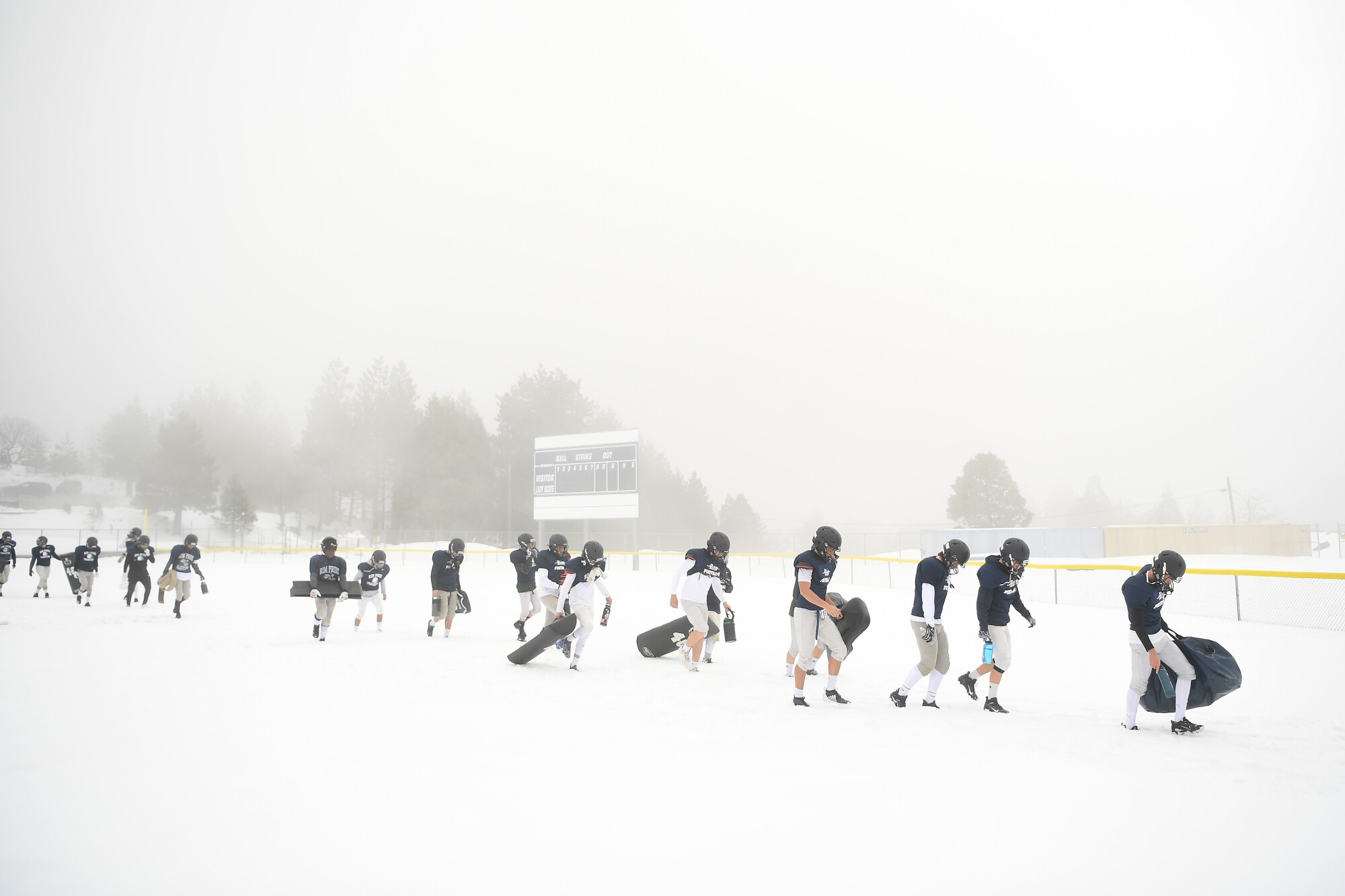 Rim of the World High School football players walk to the practice field after a snowstorm in Rimforest on Tuesday.