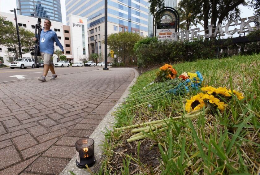 A single candle and a few flowers were left on the grass outside the Jacksonville Landing on Tuesday as the facility prepared to reopen after a mass shooting during a Madden Championship Series video game competition.