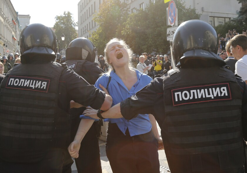 Two Russian officers wearing bulletproof vests and helmets detain a woman whose head is back and mouth is open as if in a yell.