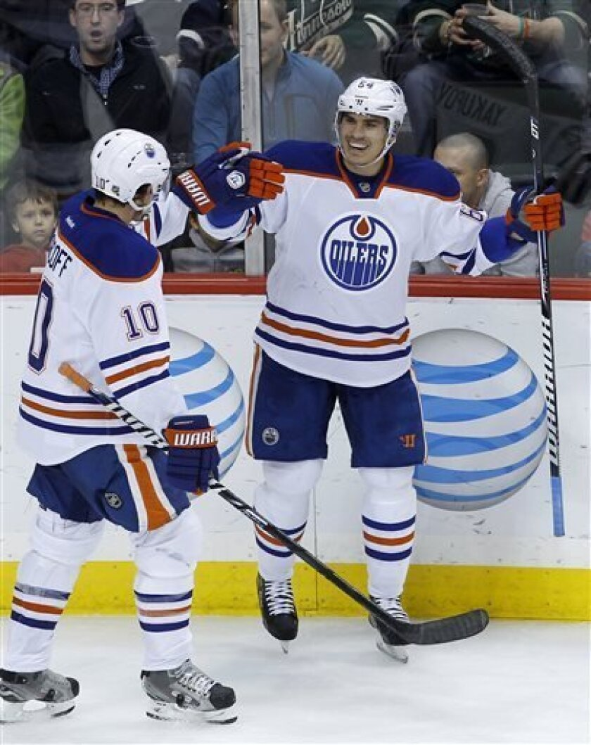 Edmonton Oilers center Shawn Horcoff (10) congratulates teammate Nail Yakupov (64), of Russia, after Yakupov scored on Minnesota Wild goalie Josh Harding during the second period of an NHL hockey game in St. Paul, Minn., Friday, April 26, 2013. (AP Photo/Ann Heisenfelt)