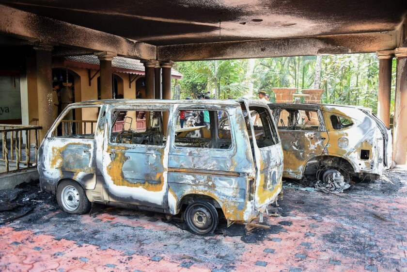 Charred vehicles outside a temple in India that was set ablaze.