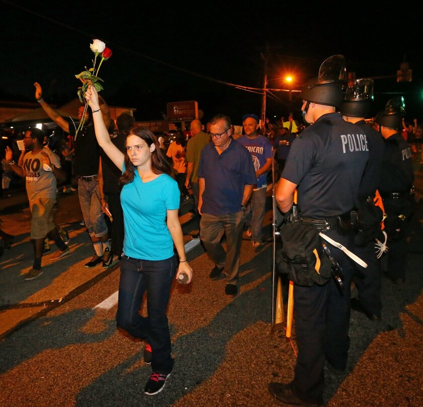 A protester holds roses in the air as she marches with others past police officers in Ferguson, Mo. on Tuesday, Aug. 19, 2014. On Saturday, Aug. 9, 2014, a white police officer fatally shot Michael Brown, an unarmed black teenager, in the St. Louis suburb. (AP Photo/Atlanta Journal-Constitution, Cu